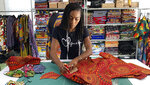 Iguehi James, an Oakland, Calif., fashion entrepreneur, cuts fabric to make a face mask she sells through her apparel company Love Iguehi, Tuesday, Sept. 15, 2020. She received a $5,000 grant from the Oakland African American Chamber of Commerce's