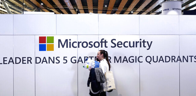 FILE - A woman walks in front of the Microsoft stand during the Cybersecurity Conference in Lille, northern France, Wednesday Jan. 29, 2020. Microsoft announced legal action Monday, Oct. 12, 2020 seeking to disrupt a major cybercrime digital network that uses more than 1 million zombie computers to loot bank accounts and spread ransomware, which experts consider a major threat to the U.S. presidential election. (AP Photo/Michel Spingler)