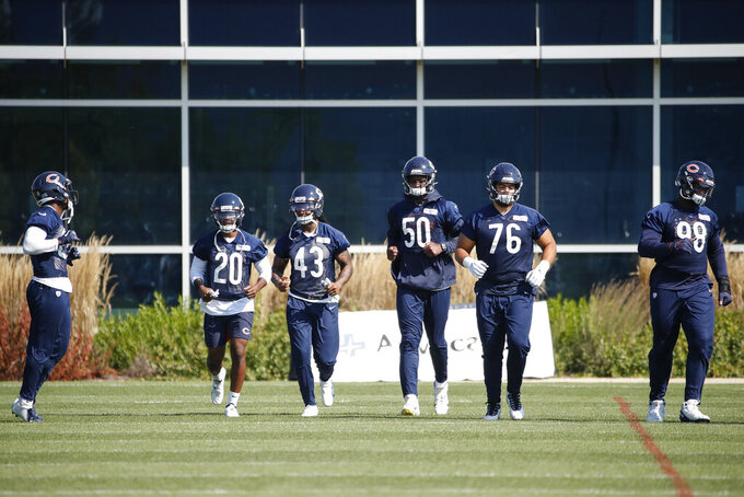 Chicago Bears cornerback Duke Shelley (20), tight end Eric Saubert (43), linebacker Barkevious Mingo (50), defensive tackle Abdullah Anderson (76) and defensive tackle Bilal Nichols (98) warm up during NFL football training camp at Halas Hall on Thursday, Sept. 3, 2020, in Lake Forest, Ill. (Kamil Krzaczynski/USA TODAY Sports via AP, Pool)