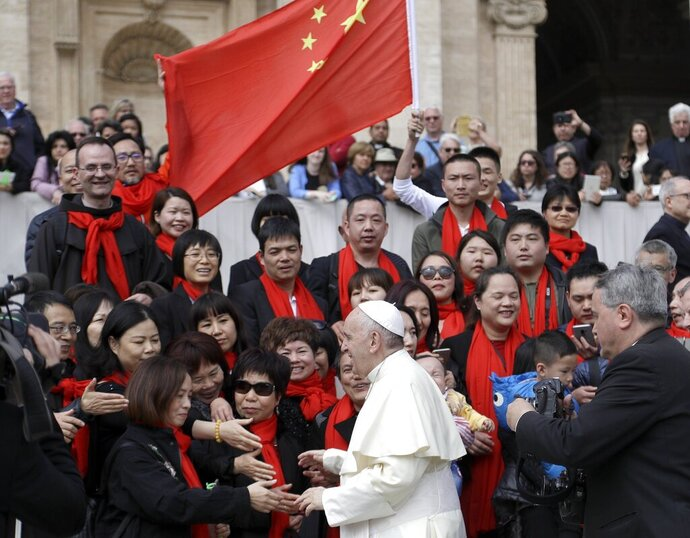 FILE - In this April 18, 2018 file photo, Pope Francis meets a group of faithful from China at the end of his weekly general audience in St. Peter's Square, at the Vatican. The Vatican on Tuesday, Sept. 29, 2020, answered its critics and justified its decision to pursue an extension of an agreement with China over bishop nominations, acknowledging difficulties but insisting that limited, positive results had been achieved.(AP Photo/Gregorio Borgia, file)