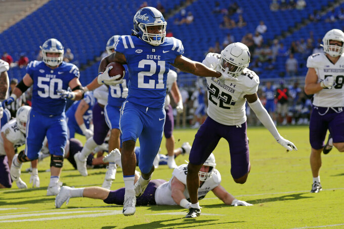 Duke running back Mataeo Durant (21) stiff-arms Northwestern defensive back Bryce Jackson (22) as he runs for a touchdown during the first half of an NCAA college football game in Durham, N.C., Saturday, Sept. 18, 2021. (AP Photo/Chris Seward)