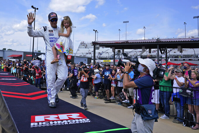 Dale Earnhardt Jr., holds his daughter Isla, 3, as he waves to the crowd during driver introductions prior to the state of the NASCAR Xfinity auto race in Richmond, Va., Saturday, Sept. 11, 2021. (AP Photo/Steve Helber)