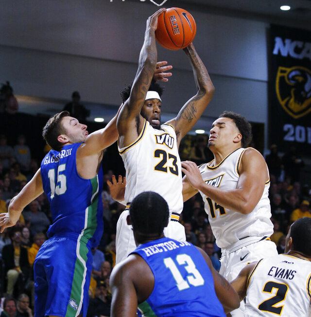 Virginia Commonwealth's Isaac Vann pulls in a rebound as Florida Gulf Coast's Sam Gagliardi reaches in during an NCAA college basketball game at Virginia Commonwealth University's Siegel Center in Richmond, Va., Saturday, Nov. 23, 2019. (Joe Mahoney/Richmond Times-Dispatch via AP)