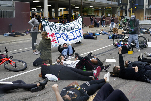 Protesters hold a die-in outside the Hennepin County Family Justice Center where four former Minneapolis police officers appeared at a hearing Friday, Sept. 11, 2020, in Minneapolis. The officers are charged in the death of George Floyd who died in police custody in May. (AP Photo/Jim Mone)