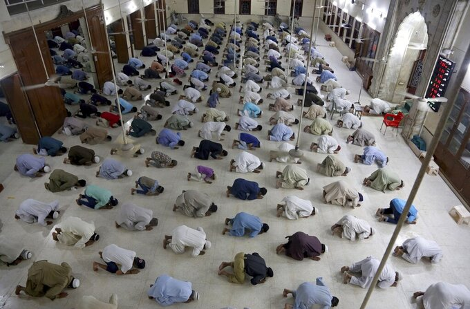 FILE- In this April 19, 2020 file photo, people attend evening prayers while maintaining a level of social distancing to help avoid the spread of the coronavirus, at a mosque in Karachi, Pakistan. The confirmed death toll from the coronavirus has gone over 50,000 in the Middle East as the pandemic continues. That's according to a count Thursday, Sept. 3, 2020, from The Associated Press, based on official numbers offered by health authorities across the region. (AP Photo/Fareed Khan, File)