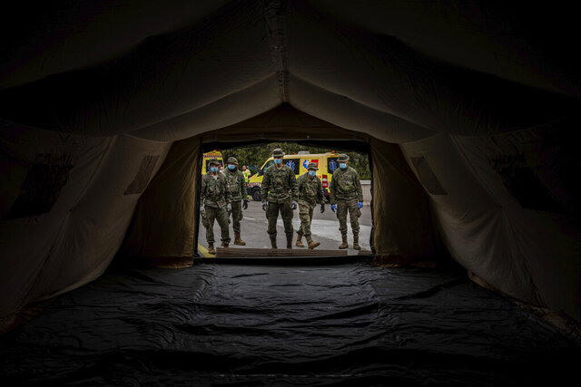 Spanish Army soldiers mount a tent to be used by hospital patients during the coronavirus outbreak in Madrid, Spain, Monday, March 30, 2020. Bells tolled in Madrid's deserted central square and flags were lowered in a day of mourning Monday as Spain raced to build field hospitals to treat an onslaught of coronavirus patients. The new coronavirus causes mild or moderate symptoms for most people, but for some, especially older adults and people with existing health problems, it can cause more severe illness or death. (AP Photo/Bernat Armangue)