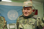 FILE - In this May 17, 1993 file photo, Bosnian Serb commander Gen. Ratko Mladic is pictured near a United Nations flag at Sarajevo Airport. U.N. judges will on Tuesday, June 8, 2021 deliver their final ruling on the conviction of former Bosnian Serb army chief Ratko Mladic on charges of genocide, war crimes and crimes against humanity during Bosnia's 1992-95 ethnic carnage. (AP Photo/Jerome Delay, File)