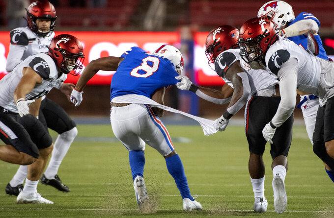 Cincinnati's Jaheim Thomas grabs the shirt of SMU kick returner Bryan Massey (8) on a kickoff return during the second half of an NCAA college football game Saturday, Oct. 24, 2020, in Dallas. Cincinnati won 42-13. (AP Photo/Jeffrey McWhorter)