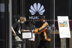 A delivery man hands over drinks near a Huawei retail store in Beijing on Monday, May 18, 2020. China's commerce ministry says it will take