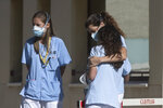 A health worker hugs her colleague during a break outside hospital in Madrid, Spain, Monday, Oct. 5, 2020. Madrid has been the source of Europe's most worrying surge of infections in the ongoing second wave of the pandemic. (AP Photo/Paul White)