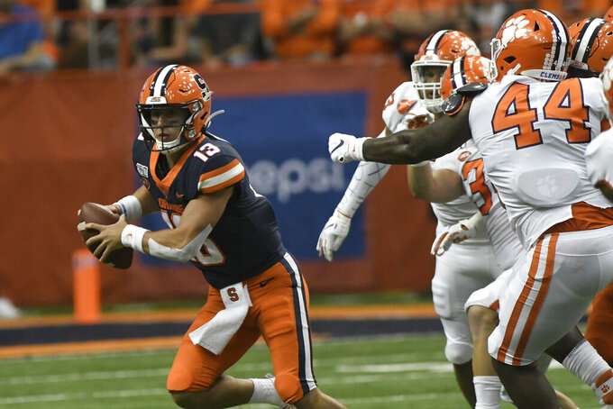 Syracuse quarterback Tommy Devito, left, scrambles away from the Clemson defense during the first half of an NCAA college football game Saturday, Sept. 14, 2019, in Syracuse, N.Y. (AP Photo/Steve Jacobs)