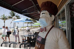 CORRECTS TO BROADWALK, INSTEAD OF BOARDWALK  A statue of a chef at Florio's of Little Italy restaurant wears a protective face mask on the Hollywood Beach Broadwalk during the new coronavirus pandemic, Thursday, July 2, 2020, in Hollywood, Fla. In hard-hit South Florida, beaches from Palm Beach to Key West will be shut down for the Fourth of July holiday weekend. Restaurants and businesses along the Boardwalk will remain open. (AP Photo/Lynne Sladky)