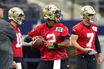 New Orleans Saints quarterback Jameis Winston (2) passes as fellow quarterbacks Taysom Hill (7) and Ian Book (16) look on during NFL football practice in Arlington, Texas, Tuesday, Aug. 31, 2021. (AP Photo/LM Otero)