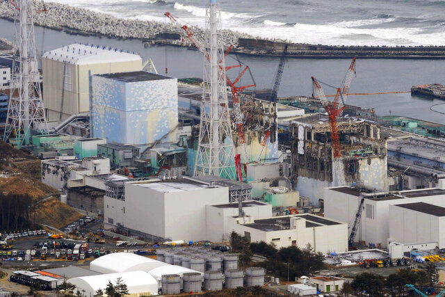 FILE - This March 11, 2012, file photo, shows three melted reactors, from left, Unit 1, Unit 2 and Unit 3 at Fukushima Dai-ichi nuclear power plant in Okuma, Fukushima prefecture, Japan. Japan revised a roadmap on Friday, Dec. 27, 2019, for the tsunami-wrecked Fukushima nuclear plant cleanup, further delaying the removal of thousands of spent fuel units that remain in cooling pools since the 2011 disaster. (Kyodo News via AP, File)
