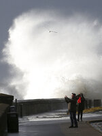 Waves batter the coastline at Saltcoats, North Ayrshire, Scotland,  Sunday, Feb. 9, 2020. Trains, flights and ferries have been cancelled and weather warnings issued across the United Kingdom as a storm with hurricane-force winds up to 80 mph (129 kph) batters the region. (Andrew Milligan/PA via AP)