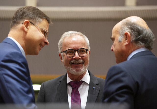 European Commissioner for An Economy that Works for People Valdis Dombrovskis, left, speaks with European Central Bank Vice-President Luis de Guindos, right, and President of the European Investment Bank Werner Hoyer during a meeting of EU finance ministers at the Europa building in Brussels, Tuesday, Feb. 18, 2020. EU finance ministers meet Tuesday to discuss tax havens. (AP Photo/Virginia Mayo)