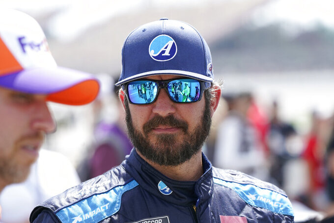 Martin Truex Jr. talks with other drivers before driver introductions at the NASCAR Cup Series auto race at Michigan International Speedway, Sunday, Aug. 22, 2021, in Brooklyn, Mich. (AP Photo/Carlos Osorio)