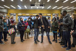 Canadian Prime Minister Justin Trudeau, center right, poses with commuters at a metro station in Montreal, Tuesday, Oct. 22, 2019. Trudeau won a second term in Canada's national elections Monday, losing the majority but delivering unexpectedly strong results despite having been weakened by a series of scandals that tarnished his image as a liberal icon. (Sean Kilpatrick/The Canadian Press via AP)