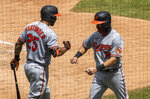 Baltimore Orioles' Anthony Santander, left, gives teammate Pat Valaika, right, an elbow-bump after Valaika scored a run on Hanser Alberto's two-run double during the fifth inning of a baseball game against the Washington Nationals in Washington, Sunday, Aug. 9, 2020. (AP Photo/Manuel Balce Ceneta)