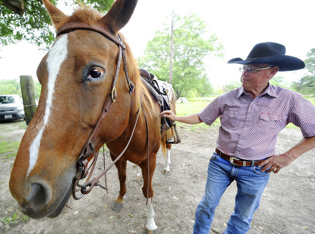 In this April 17, 2020, photo, Allen Rush, a certified equine therapist, introduces therapy horse Sister at 4R Farms in Burke, Texas. As spring continues to sprout in earnest, the horse family at 4R Farm offers a mental health haven to those seeking relief, especially during a time of tribulation like the current pandemic. (Joel Andrews/The Daily News via AP)