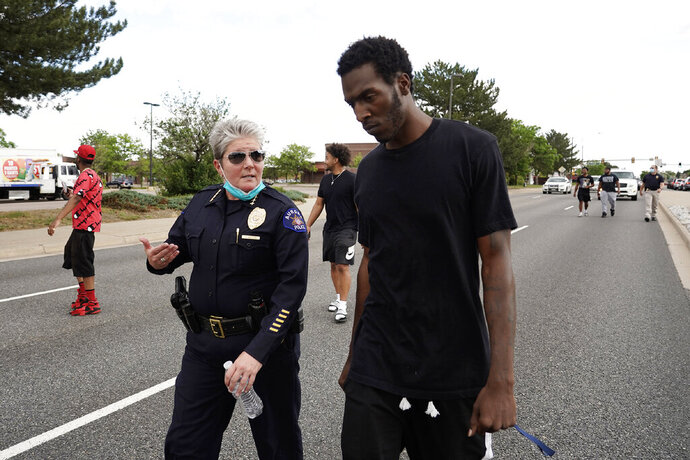 FILE - In this June 2, 2020, file photo, interim Aurora Police Chief Vanessa Wilson and Jay B. confer as protesters march north on South Chambers Road during a peaceful protest against police brutality following the death of George Floyd in Aurora, Colo. Multiple suburban Denver police officers have been placed on paid administrative leave amid an investigation into photos of them related to the case of a Black man who died last summer after he was stopped and restrained, police said Monday, June 29. Wilson said in a statement that the suspended officers were