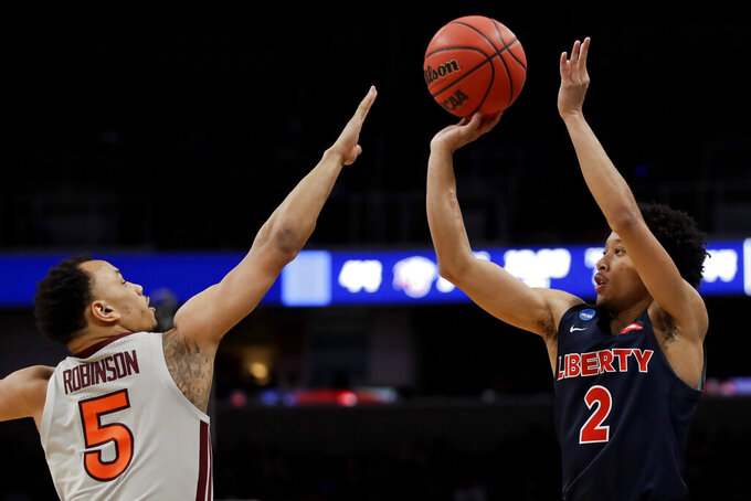Liberty guard Darius McGhee, right, shoots over Virginia Tech guard Justin Robinson during the second half of a second-round game in the NCAA men's college basketball tournament Sunday, March 24, 2019, in San Jose, Calif. (AP Photo/Ben Margot)