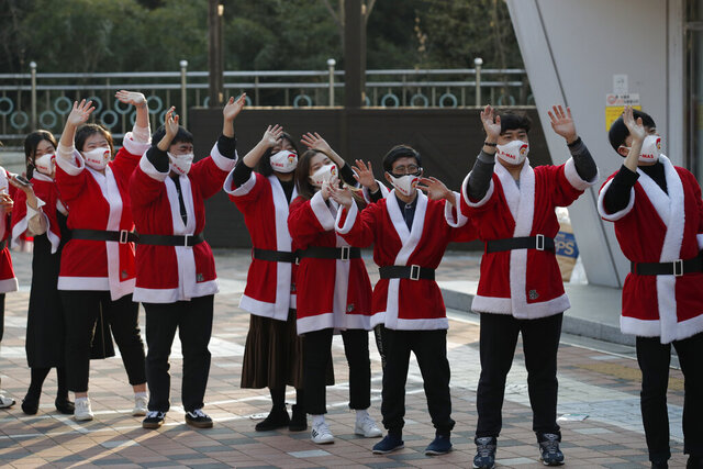 Volunteers wearing face masks wave after they load boxes onto a delivery truck during an event to send Christmas gifts for the underprivileged in Seoul, South Korea, Tuesday, Dec. 22, 2020. The Korea Youth Foundation sent Christmas gifts using a courier to help prevent against the coronavirus as the social distancing measures. (AP Photo/Lee Jin-man)
