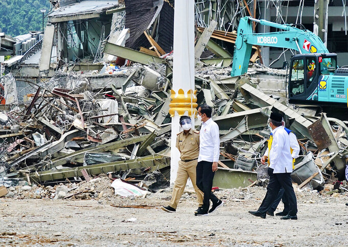 In this photo released by the Indonesian Presidential Palace, President Joko Widodo, center, talks to an official as he inspects an earthquake-damaged government building, in Mamuju, West Sulawesi, Indonesia, Tuesday, Jan. 19, 2021. Widodo visited the areas where a deadly earthquake left thousands of people homeless in an effort to reassure them the government's response is reaching those struggling after the quake. (Indonesian Presidential Palace via AP)