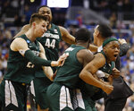 Michigan State guard Cassius Winston, right, celebrates with teammates Matt McQuaid (20), Nick Ward (44) and Gabe Brown (13) after defeating Duke in an NCAA men's East Regional final college basketball game in Washington, Sunday, March 31, 2019. (AP Photo/Patrick Semansky)