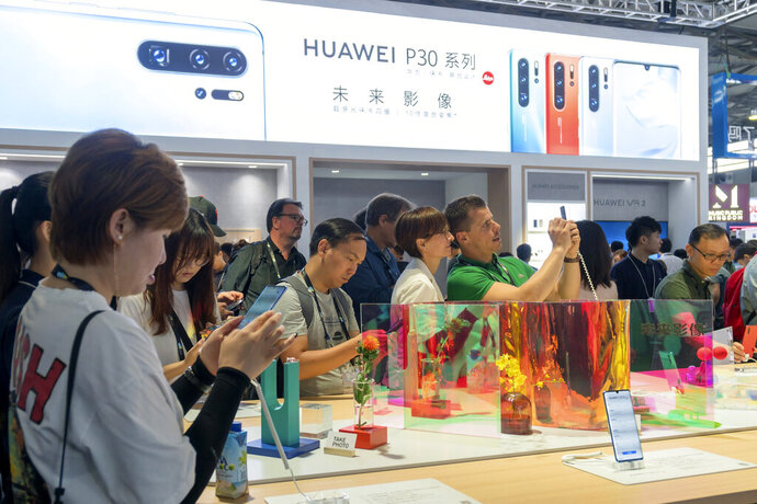 Visitors look at a display of smartphones from Chinese technology firm Huawei at the Consumer Electronics Show in Shanghai, Tuesday, June 11, 2019. Chinese tech giant Huawei said Tuesday it would have become the world's number one smartphone maker by year's end if it were not for