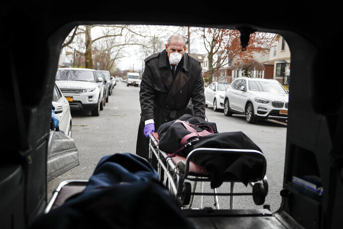 """Funeral director Tom Cheeseman loads a body into his van after making a house call, Friday, April 3, 2020, in the Brooklyn borough of New York. The Associated Press spent a day on the road with Cheeseman, who is overwhelmed by demand due to the coronavirus outbreak. Cheeseman is picking up as many as 10 bodies per day. Most bodies come from homes and hospitals. """"We took a sworn oath to protect the dead, this is what we do,"""" he said. (AP Photo/John Minchillo)"""