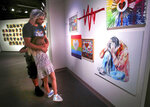 In a  Monday, June 3, 2019 photo, Bryan Formica, visiting from Cape Coral, Fla., embraces his daughter Marley, 8, as they visit the new 'Love Speaks' exhibit —artists' reflections on the Pulse nightclub massacre— at the Orange County Regional History Center in Orlando, Fla. The exhibit opened June 1, ahead of the third anniversary of the mass shooting that killed 49 people. (Joe Burbank/Orlando Sentinel via AP)