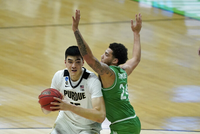 Purdue's Zach Edey (15) goes to the basket against North Texas's Zachary Simmons (24) during the first half of a first-round game in the NCAA men's college basketball tournament at Lucas Oil Stadium, Friday, March 19, 2021, in Indianapolis. (AP Photo/Darron Cummings)