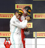 Mercedes driver Lewis Hamilton, left, of Britain, winner of the French Formula One Grand Prix, celebrates on the podium with third placed Ferrari driver Charles Leclerc of Monaco, at the Paul Ricard racetrack, in Le Castellet, southern France, Sunday, June 23, 2019. (AP Photo/Claude Paris)