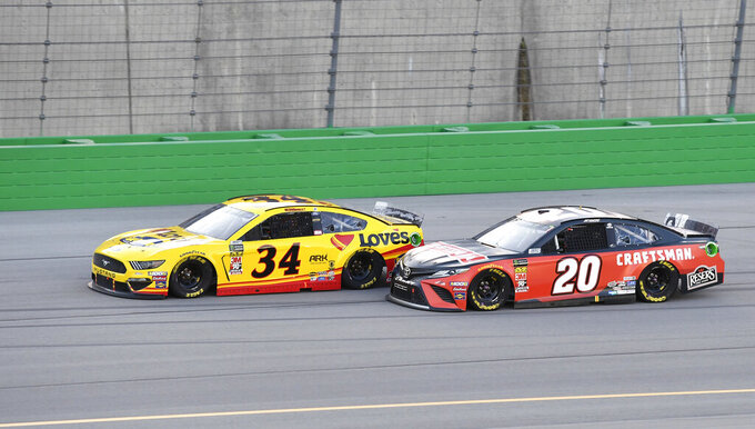 Erik Jones (20) drives next to Michael McDowell (34) during the NASCAR Cup Series auto race at Kentucky Speedway in Sparta, Ky., Saturday, July 13, 2019. (AP Photo/Timothy D. Easley)