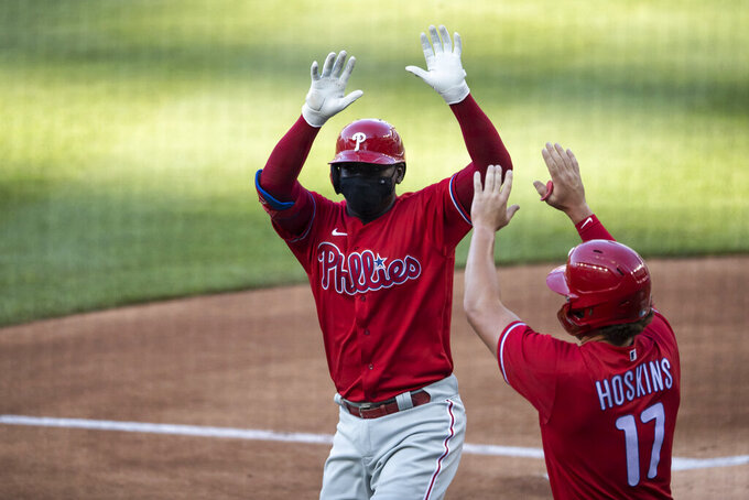 Philadelphia Phillies' Didi Gregorius celebrates without touching, while wearing a mask, his three-run homer with Rhys Hoskins during the first inning of an exhibition baseball game against the Washington Nationals at Nationals Park, Saturday, July 18, 2020, in Washington. (AP Photo/Alex Brandon)