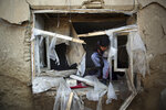 FILE- in this Dec. 11, 2019, photo, a boy inspect his damaged home after after an attack near the Bagram Air Base In Parwan province of Kabul, Afghanistan, A United Nations report says Afghanistan passed a grim milestone with more than 100,000 civilians killed or hurt in the last 10 years since the international body began documenting casualties in a war that has raged for 18 years. (AP Photo/Rahmat Gul, file)