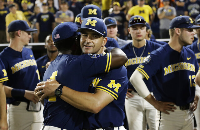 FILE - In this June 26, 2019, file photo, Michigan coach Erik Bakich, center, is hugged by Michigan's Ako Thomas (4) as they watch Vanderbilt celebrate after Vanderbilt defeated Michigan to win Game 3 of the NCAA College World Series baseball finals in Omaha, Neb. As disappointing as it's been to have the college baseball season shut down because of the coronavirus pandemic, Michigan coach Erik Bakich sees a silver lining.