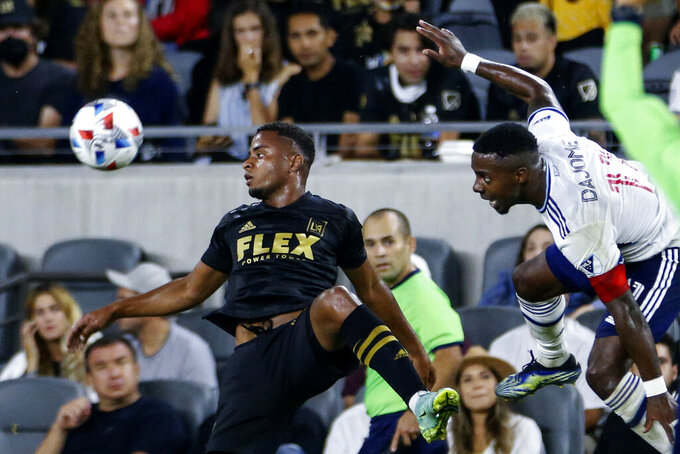 Vancouver Whitecaps midfielder Cristian Dajome, right, and Los Angeles FC defender Diego Palacios watch the ball during the second half of an MLS soccer match in Los Angeles, Saturday, July 24, 2021. The game ended in a 2-2 draw. (AP Photo/Ringo H.W. Chiu)