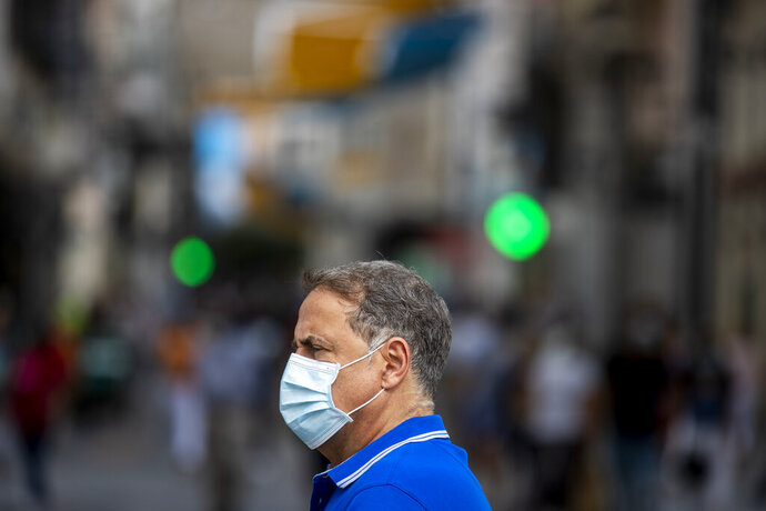 A man wearing a face mask to prevent the spread of coronavirus stands in downtown Madrid, Spain, Wednesday, Sept. 16, 2020. The Spanish capital will introduce selective lockdowns in urban areas where the coronavirus is spreading faster, regional health authorities announced on Tuesday. (AP Photo/Manu Fernandez)