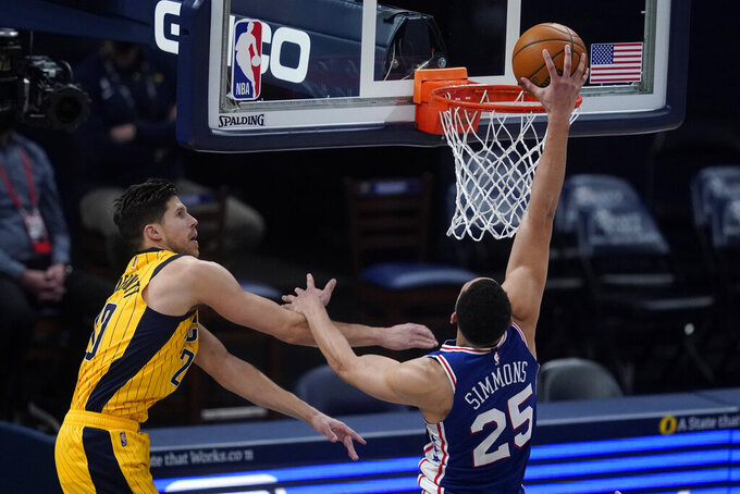 Philadelphia 76ers' Ben Simmons (25) dunks against Indiana Pacers' Doug McDermott (20) during the second half of an NBA basketball game, Tuesday, May 11, 2021, in Indianapolis. (AP Photo/Darron Cummings)