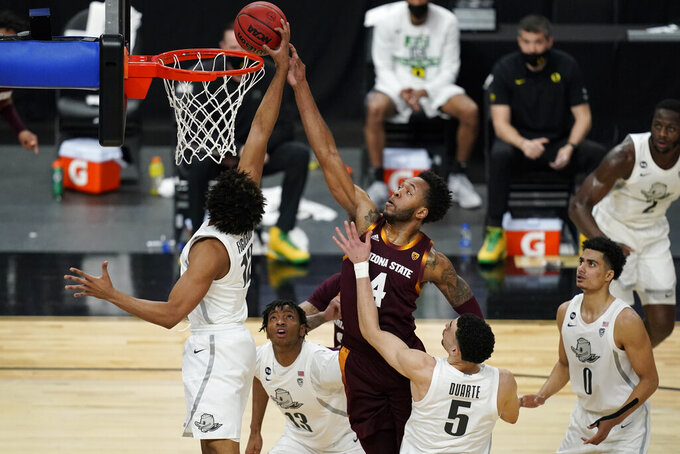 Arizona State's Kimani Lawrence (4) shoots against Oregon's LJ Figueroa (12) during the first half of an NCAA college basketball game in the quarterfinal round of the Pac-12 men's tournament Thursday, March 11, 2021, in Las Vegas. (AP Photo/John Locher)