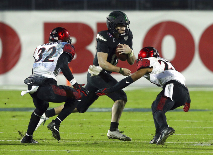 Ohio quarterback Nathan Rourke (12) carries the ball against San Diego State cornerback Tayler Hawkins (32) and cornerback Kyree Woods (27) in the second half of the Frisco Bowl NCAA college football game, Wednesday, Dec. 19, 2018, in Frisco, Texas. (AP Photo/Richard W. Rodriguez)