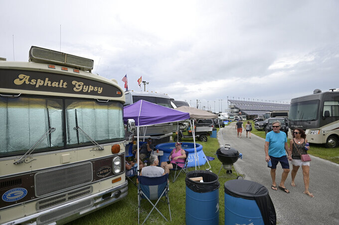 Fans hang out in the infield campground before a NASCAR Xfinity Series auto race at Daytona International Speedway, Friday, Aug. 27, 2021, in Daytona Beach, Fla. (AP Photo/Phelan M. Ebenhack)