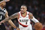 Brooklyn Nets guard Spencer Dinwiddie, left, defends against Portland Trail Blazers guard Damian Lillard during the first half of an NBA basketball game in Portland, Ore., Monday, March 25, 2019. (AP Photo/Randy L. Rasmussen)