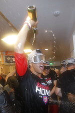 Washington Nationals left fielder Juan Soto celebrates in the locker room after the team's 7-3 win against the Los Angeles Dodgers in 10 innings in Game 5 of a baseball National League Division Series on Wednesday, Oct. 9, 2019, in Los Angeles. (AP Photo/Marcio Jose Sanchez)