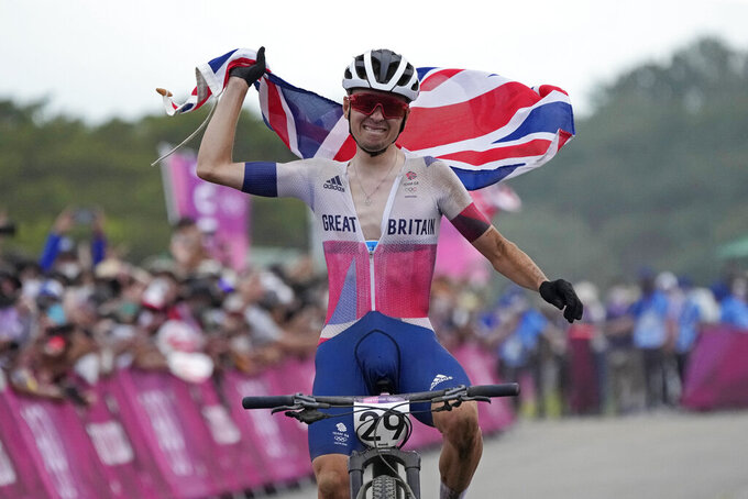 Thomas Pidcock of Britain celebrates as he wins the gold medal during the men's cross country mountain bike competition at the 2020 Summer Olympics, Monday, July 26, 2021, in Izu, Japan. (AP Photo/Christophe Ena)