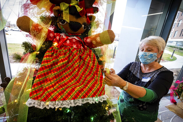 Patricia Toth works to decorate a tree ahead of this year's Festival of Trees Friday, Nov. 20, 2020 in Port Huron, Mich. McLaren Port Huron Foundation will host the Festival of Trees for the 32nd year this holiday season, but the event is going to look a little different due to the COVID-19 pandemic. (Brian Wells/The Times Herald via AP)