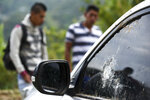 People gather around a car riddled by bullets on the road leading to Tacueyo, in southwest Colombia, Wednesday, Oct. 30, 2019. Five indigenous leaders of the Tacueyo reservation were killed late Tuesday when the vehicles they were traveling in were ambushed by gunmen the government says are part of a dissident front of Revolutionary Armed Forces of Colombia. (AP Photo/Christian Escobar Mora)