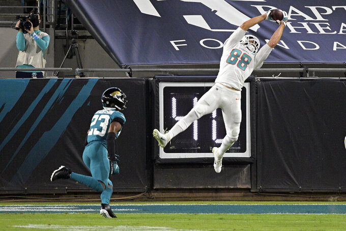 Miami Dolphins tight end Mike Gesicki (88) makes a reception in front of Jacksonville Jaguars cornerback C.J. Henderson (23) during the first half of an NFL football game, Thursday, Sept. 24, 2020, in Jacksonville, Fla. (AP Photo/Phelan M. Ebenhack)